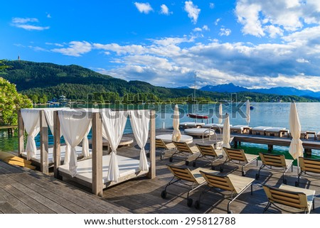 Sunchairs and beds on wooden deck and view of beautiful alpine lake Worthersee in summer time, Austria - stock photo
