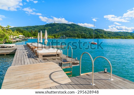 Sunchairs on public promenade and view of beautiful alpine lake Worthersee in summer, Austria - stock photo