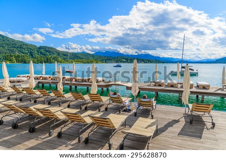 Sunchairs on wooden deck and view of beautiful alpine lake Worthersee in summer, Austria - stock photo
