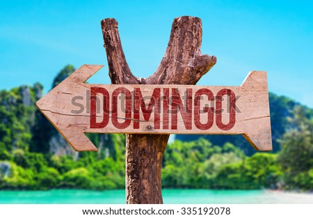 Sunday (in Spanish and Portuguese) arrow with beach background - stock photo