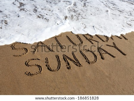 Sunday is coming concept - inscription Saturday and Sunday written on a sandy beach, the wave is starting to cover the word Saturday.  - stock photo