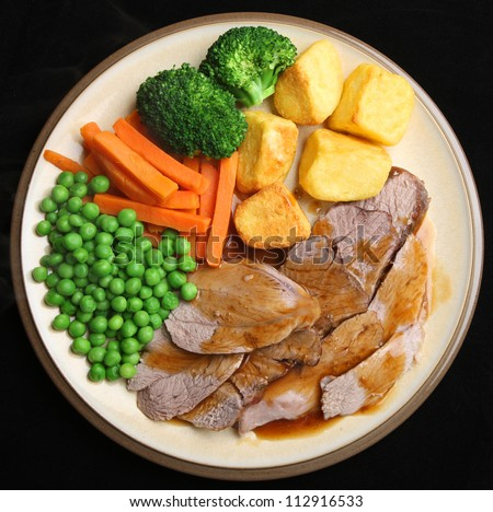 Sunday roast lamb dinner with roast potatoes, broccoli, peas, carrots and gravy.