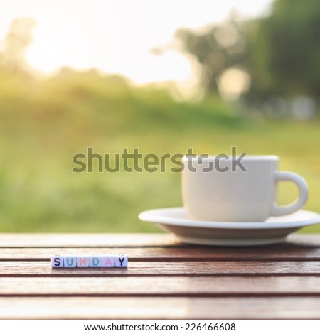 Sunday written in letter beads and a coffee cup on table - stock photo