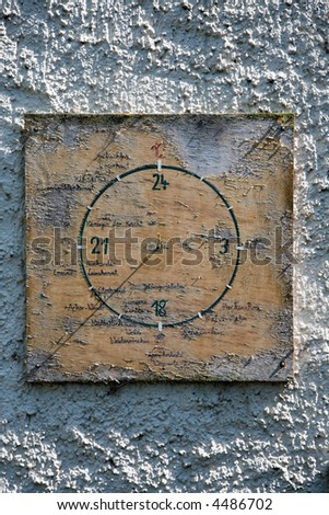 Sundial on a concrete wall. - stock photo