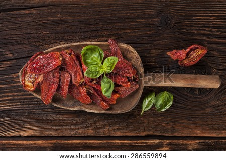 Sundried tomatoes and fresh basil leaves on brown wooden background. Culinary italian eating.  - stock photo