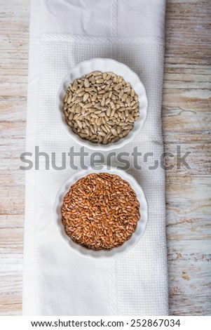 Sunflower and linseed in white bowls - stock photo