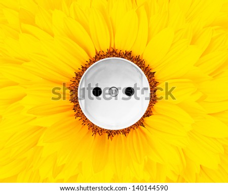 Sunflower combined with a convenience outlet symbolizing sun energy - stock photo