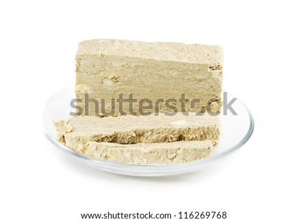 Sunflower Halva with peanuts on a glass saucer isolated on white background. Eastern sweets.