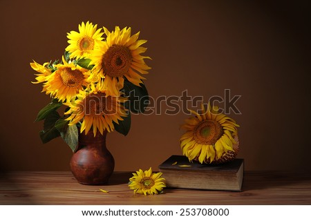 Sunflower in a ceramic vase, books and wicker basket on the table - stock photo