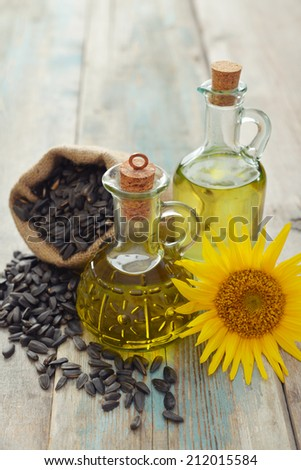 Sunflower oil in bottles with  seeds and flower on wooden background - stock photo