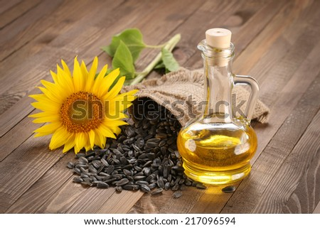 sunflower oil, seed and sunflower on the background of wooden boards - stock photo