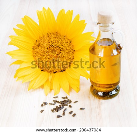 Sunflower oil with seeds on the wooden table and white background. - stock photo