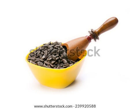 Sunflower seed in bowl with wooden scoop on white background - stock photo