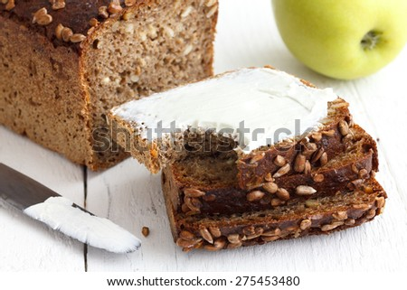Sunflower seed loaf sliced, cream cheese spread, rustic surface, apple. - stock photo