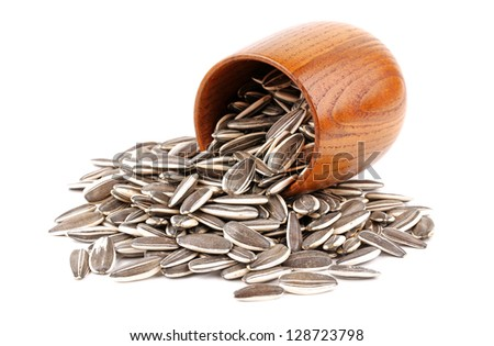 sunflower seeds in wooden cup isolated on white background - stock photo