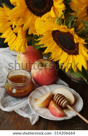 Sunflowers, apple and honey on a wooden table - stock photo