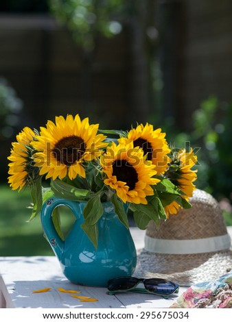 Sunflowers in ceramic vase in a garden with hat and sunglasses