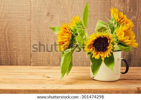 Sunflowers in vintage cup on wooden table. Autumn background