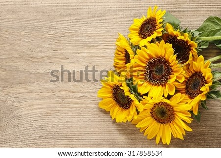 Sunflowers on wooden background - stock photo