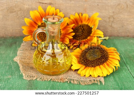 Sunflowers with oil on wooden background