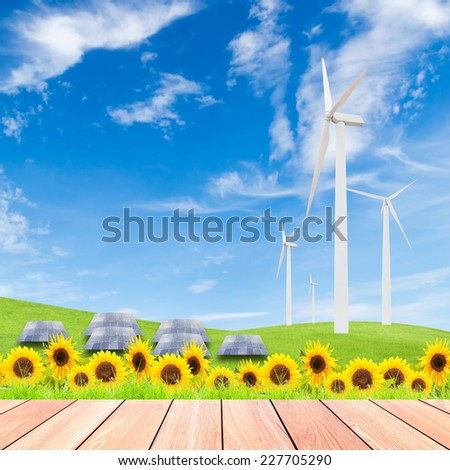 sunflowers with wind turbine and solar panels on green grass field against blue sky background and wood plank foreground,used for green earth concept - stock photo