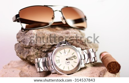 Sunglasses and a cigar laying on a limestone rock
