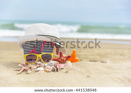 Sunglasses and a hat on a background of sea shells on. - stock photo