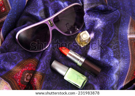 sunglasses and accessories on silky scarf - stock photo