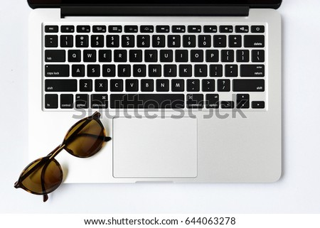 Sunglasses and computer keyboard on white background - taken in natural light with strong shadow to create realistic indoor mood