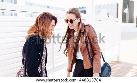 sunglasses and fancy closes are enjoying their walk. One girl with unbounded brown hair is wearing black jacked above motley dress. Another girl is wearing brown leather jecket above titer blouse - stock photo