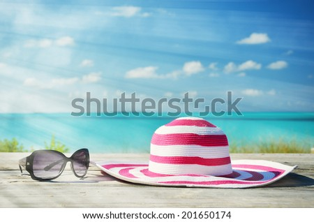 Sunglasses and hat against ocean - stock photo