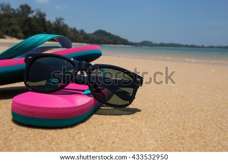 sunglasses  and pink flip flops on the beach. - stock photo