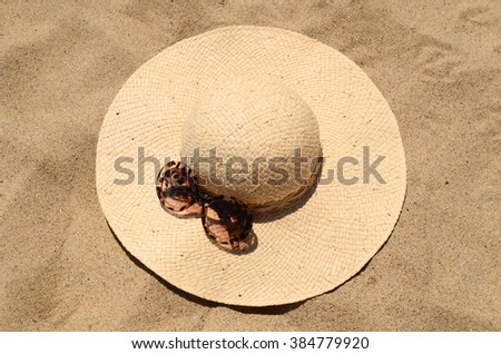 Sunglasses and straw hat lying on the sand - stock photo