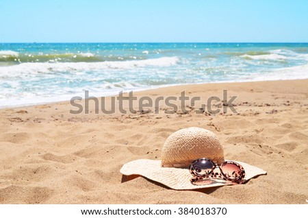 Sunglasses and straw hat lying on the sand on a beach against the sea - stock photo