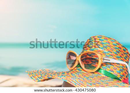 sunglasses and straw hat with blur sea and sky background