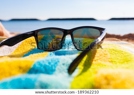 Sunglasses at the beach. Tropical beach vacation holiday and travel concept. - stock photo