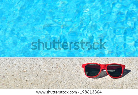Sunglasses beside the swimming pool  - stock photo