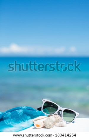 Sunglasses, blue scarf and seashells lying on blue ocean background - stock photo