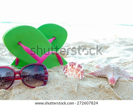 Sunglasses,flip-flop on the sand. summer holiday's concept. - stock photo