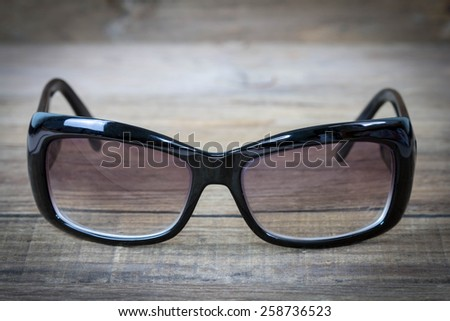 Sunglasses isolated against a wood background