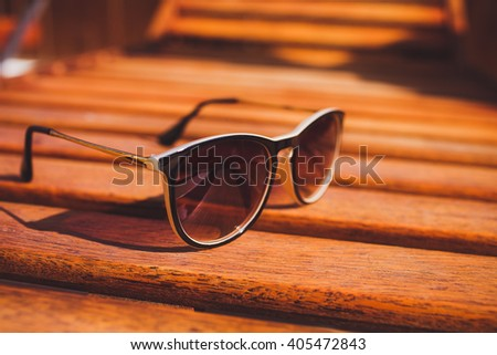 sunglasses lie  on brown  sun lounger wood