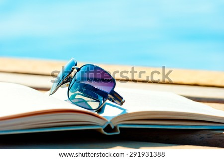sunglasses lying on an open book - stock photo