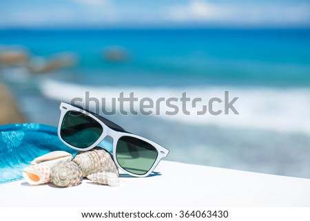sunglasses lying on tropical sand beach. party. white towel on desk and red glasses with seashells. Sunglasses on the beach. Beautiful sea view wallpaper, background - stock photo
