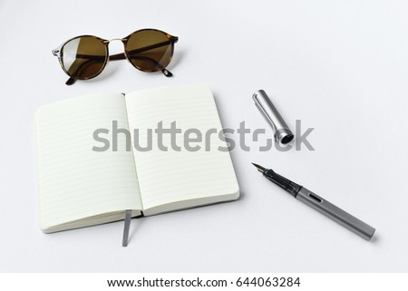 Sunglasses, notebook, and pen, on white background - taken in natural light with strong shadow to create realistic indoor mood