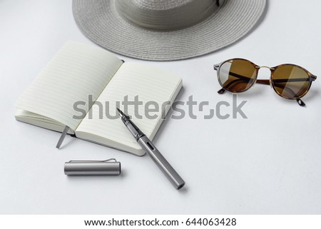 Sunglasses, notebook, pen, and hat, on white background - taken in natural light with strong shadow to create realistic indoor mood