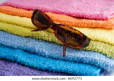 sunglasses on a pile of multicolor towels - stock photo