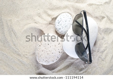 Sunglasses on a stone at the beach.