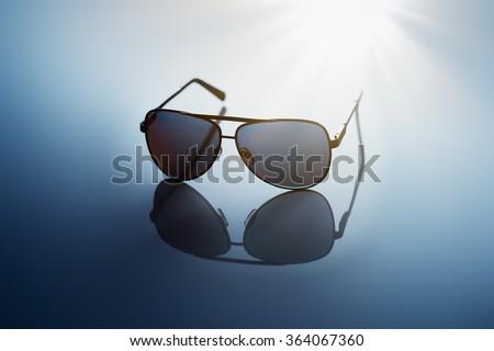 Sunglasses on blue reflective background. - stock photo