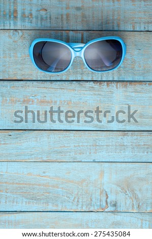 Sunglasses on blue wood.Summer holiday background concept - stock photo