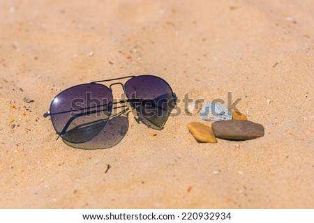sunglasses on sand - stock photo